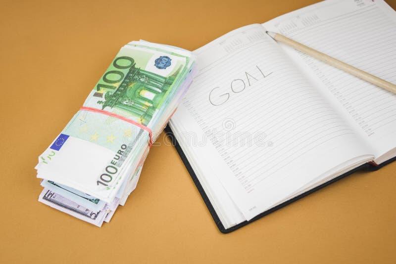 caderno branco em de madeira o fundo de cem fins do dinheiro do euro acima imagens de stock royalty free