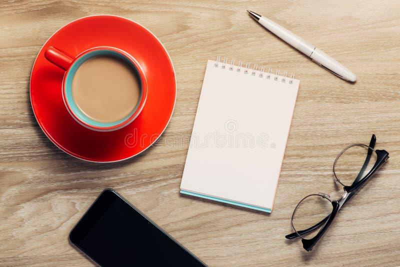 Caderno branco vazio aberto, monóculo, pena e xícara de café na mesa imagem de stock royalty free