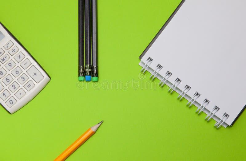 Caderno, calculadora e lápis pretos em um fundo verde, vista superior imagens de stock
