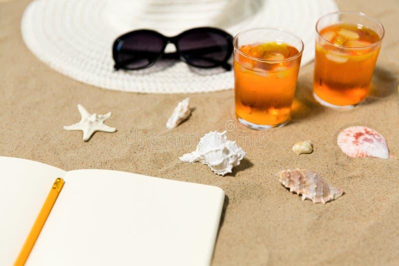 Caderno, cocktail, chapéu e máscaras na areia da praia imagens de stock