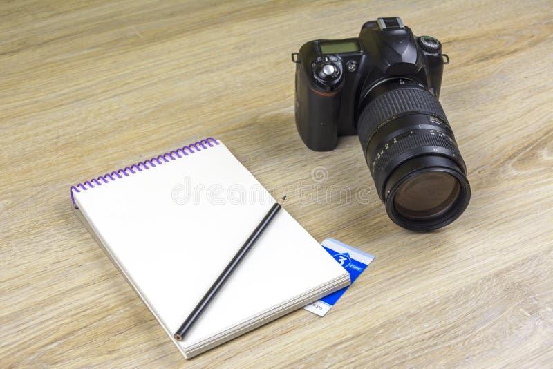 Caderno com a câmera dos lápis e da foto de SLR na textura de madeira imagens de stock
