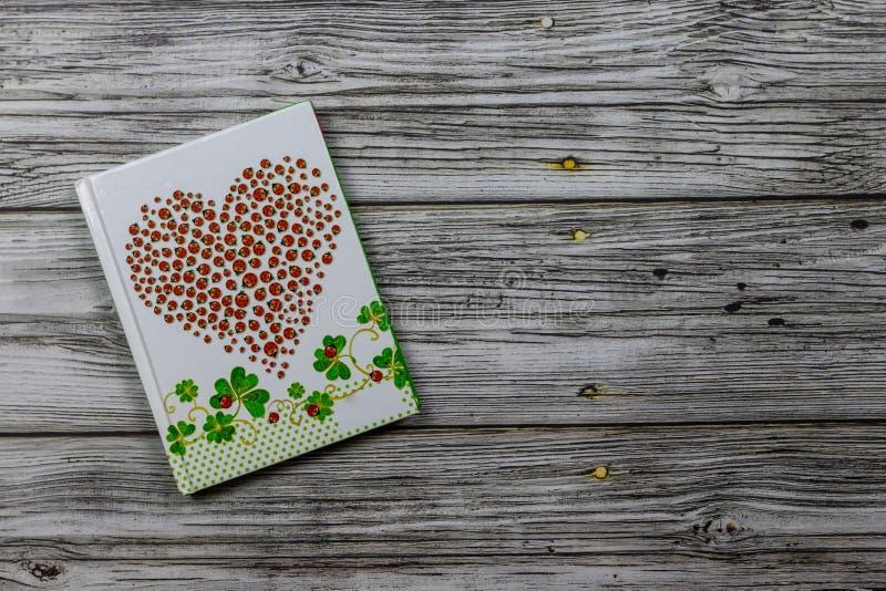 Caderno com coração vermelho dos joaninhas No fundo de madeira, foto acima Feriado, o dia de Valentim imagem de stock royalty free
