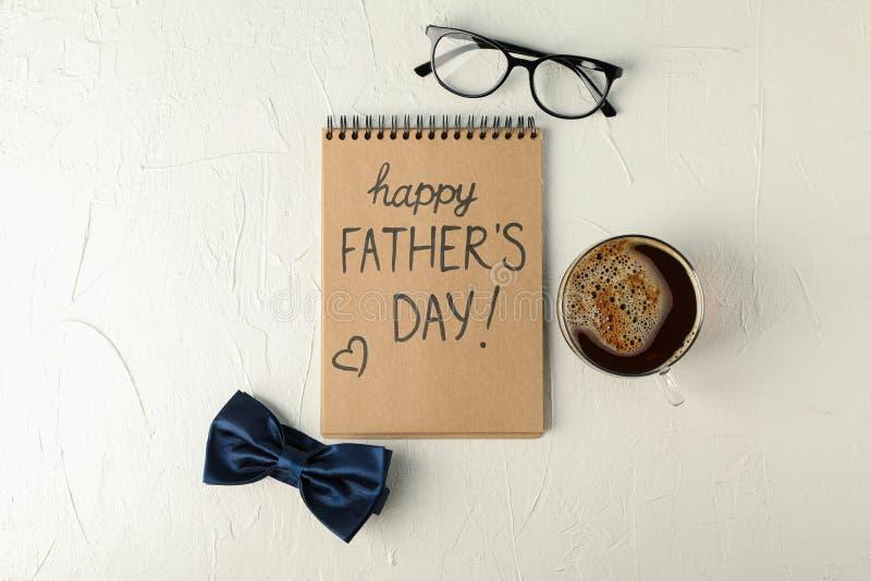 Caderno com dia de pais feliz da inscrição, laço azul, xícara de café e vidros no fundo branco foto de stock royalty free