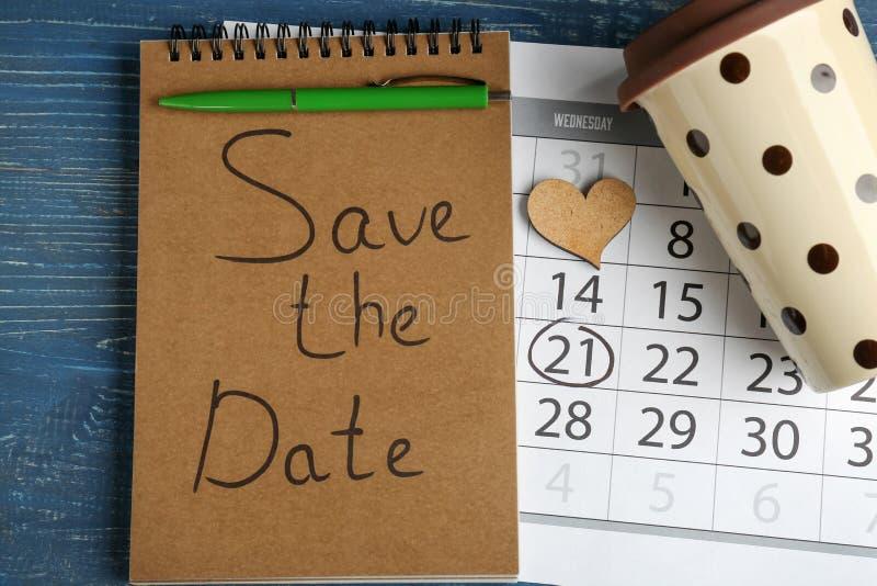 """Caderno com inscrição \ """"economias a data \"""", calendário e copo no fundo de madeira da cor imagens de stock"""
