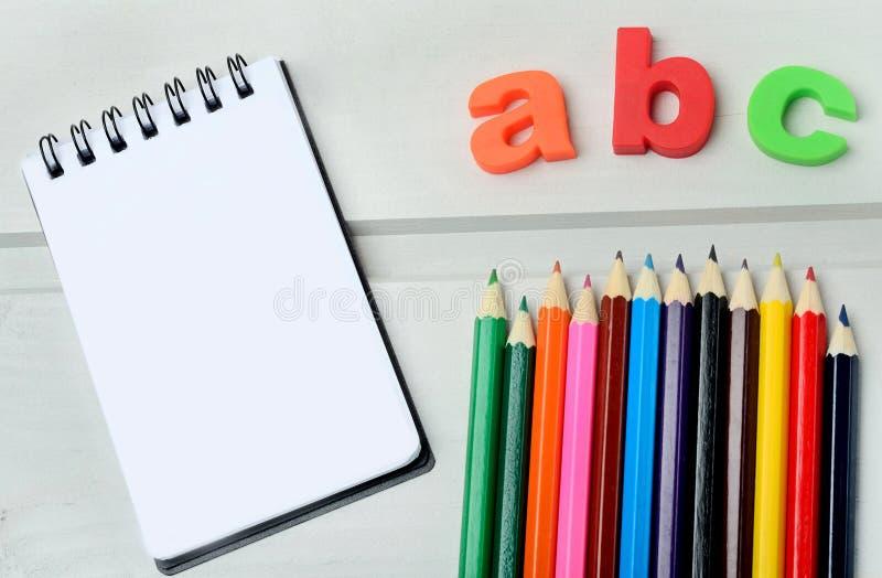Caderno com lápis coloridos fotografia de stock royalty free