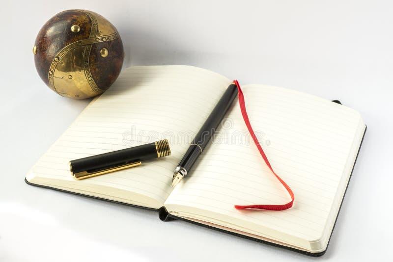 Caderno com pena de fonte e objeto esférico foto de stock