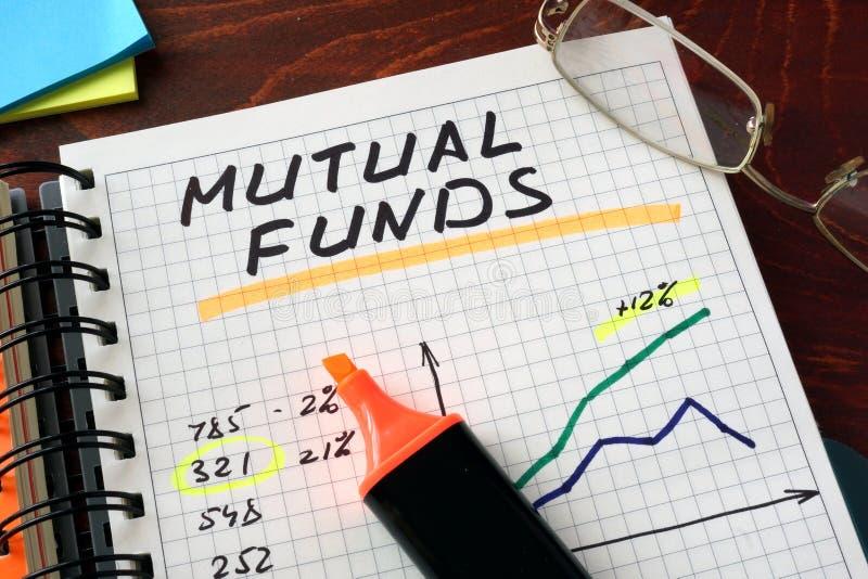 Caderno com sinal dos fundos de investimento aberto em uma tabela fotografia de stock royalty free