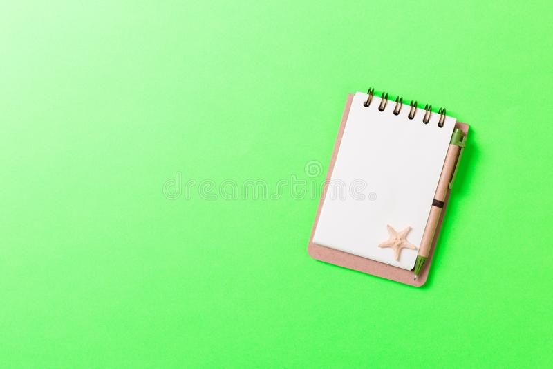 Caderno com sseashells na configuração lisa da opinião superior do fundo do rosa Conceito planejando das férias de verão, do turi fotos de stock
