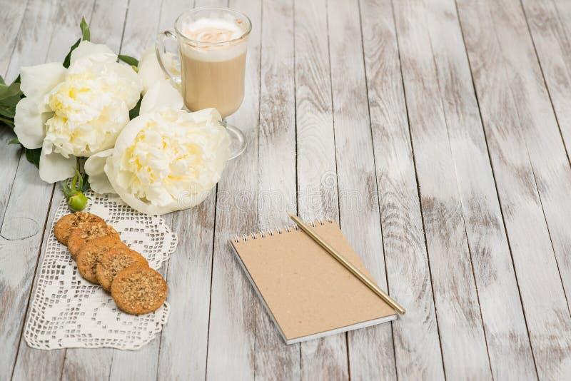 Caderno com um lápis ao lado do vidro do cappuccino e das cookies no fundo de madeira branco Lugar para o texto foto de stock royalty free