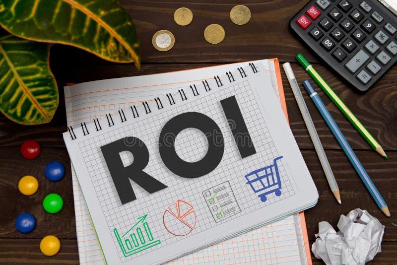 Caderno com um ROI das notas na tabela do escritório com ferramentas fotografia de stock royalty free