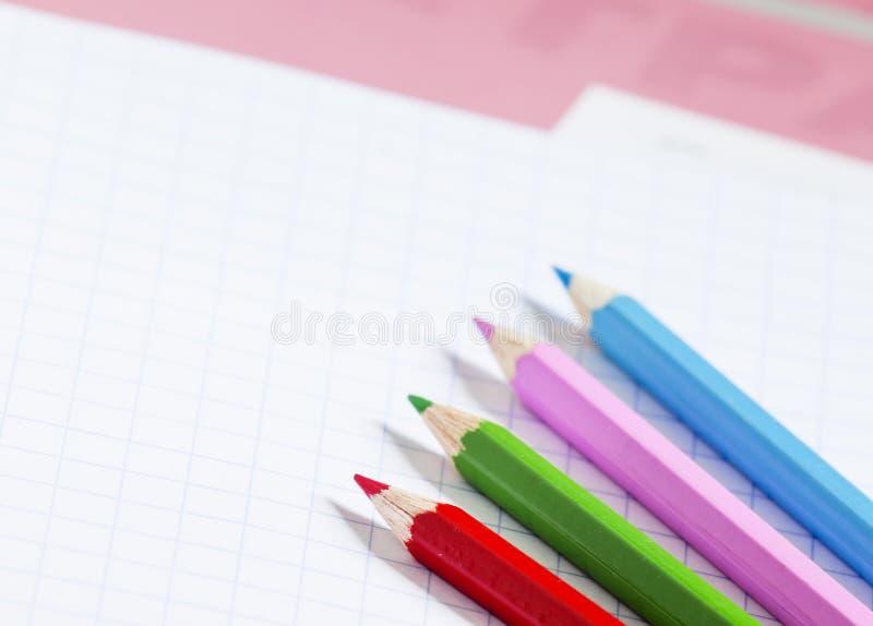 Caderno cor-de-rosa da escola na caixa e nos lápis coloridos, f seletivo imagem de stock royalty free