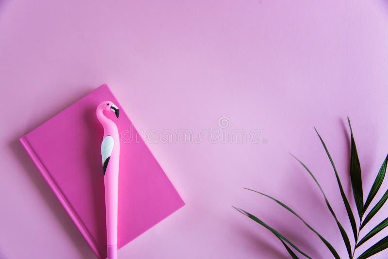 Caderno cor-de-rosa para notas, a pena engraçada do flamingo e folhas de palmeira verdes no fundo pastel cor-de-rosa Configuração imagens de stock