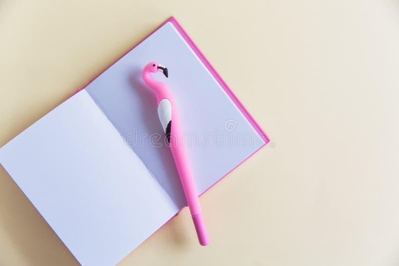 Caderno cor-de-rosa para notas, pena engraçada do flamingo no fundo pastel cor-de-rosa Configuração lisa Vista superior Copie o e foto de stock royalty free