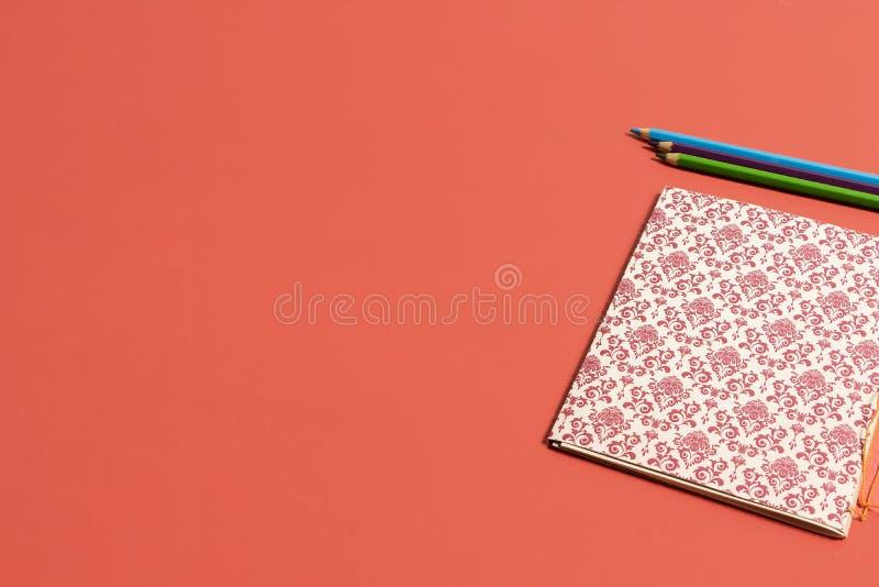 Caderno coral vivo da cor com o teste padrão do renascimento acompanhado dos lápis azuis e verdes foto de stock