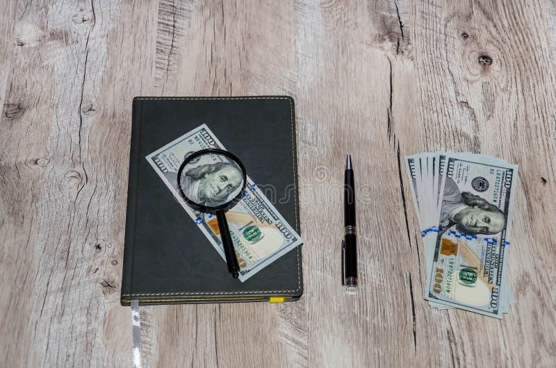 Caderno, dólares, lente de aumento e pena cinzentos em uma tabela de madeira fotografia de stock