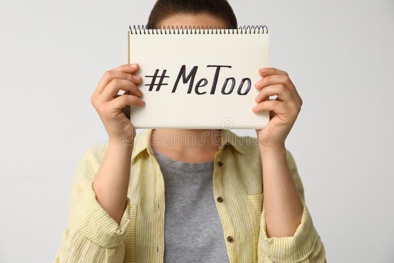 Caderno da terra arrendada da mulher com o hashtag imitação contra o fundo claro Agressão sexual da parada imagem de stock