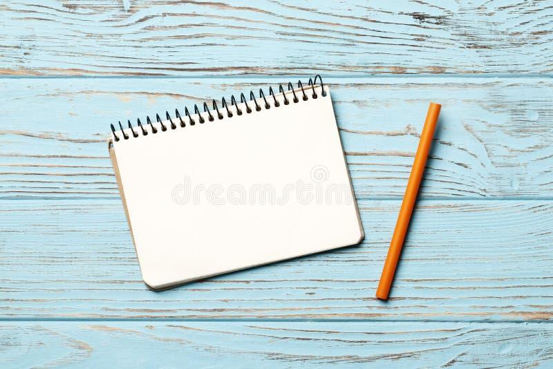 caderno de papel com a pena no fundo de madeira azul imagens de stock