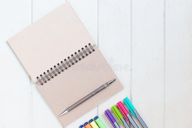 Caderno de papel vazio com muitos highlighter da cor na placa de madeira branca foto de stock