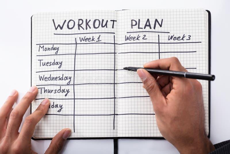 Caderno de Person Filling Workout Plan In foto de stock
