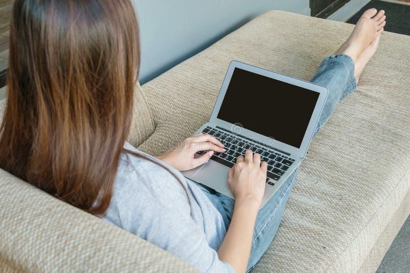 Caderno do computador do close up no regaço da mulher com assento no sofá para a ação do trabalho no conceito autônomo do trabalh imagens de stock
