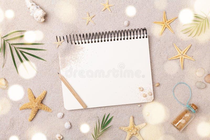 Caderno dos viajantes com os acessórios na opinião superior do fundo da areia Conceito planejando das férias de verão, da viagem  imagem de stock