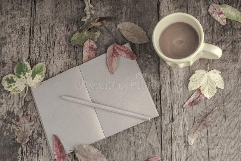 Caderno e café na tabela de madeira decorada com folhas secadas imagem de stock royalty free