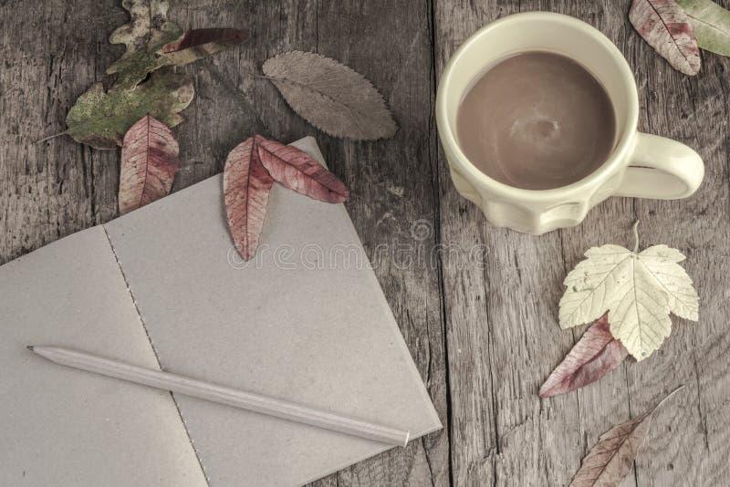 Caderno e café na tabela de madeira decorada com folhas secadas imagens de stock