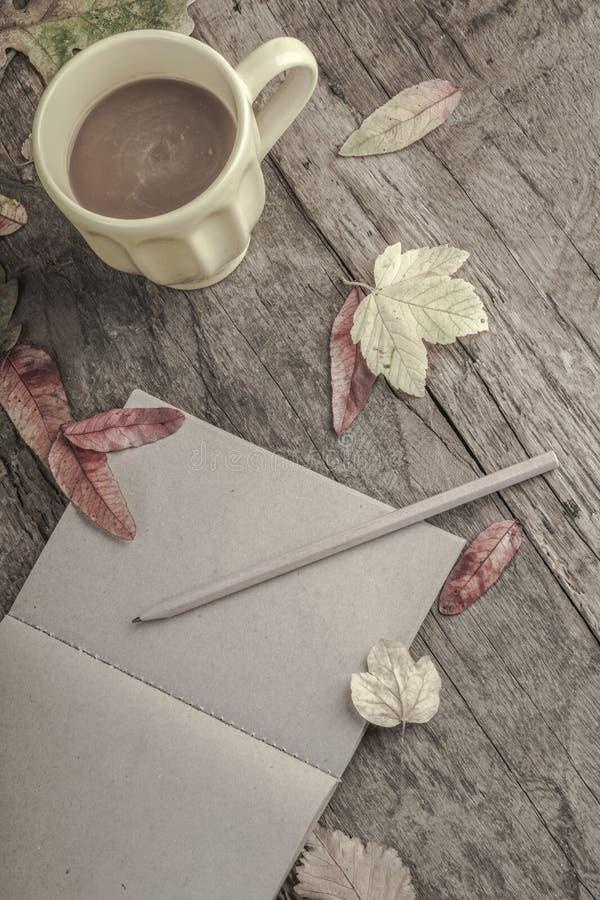 Caderno e café na tabela de madeira decorada com folhas secadas fotografia de stock