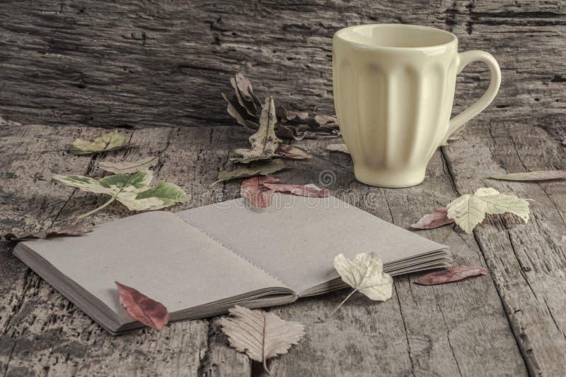 Caderno e café na tabela de madeira decorada com folhas secadas imagem de stock