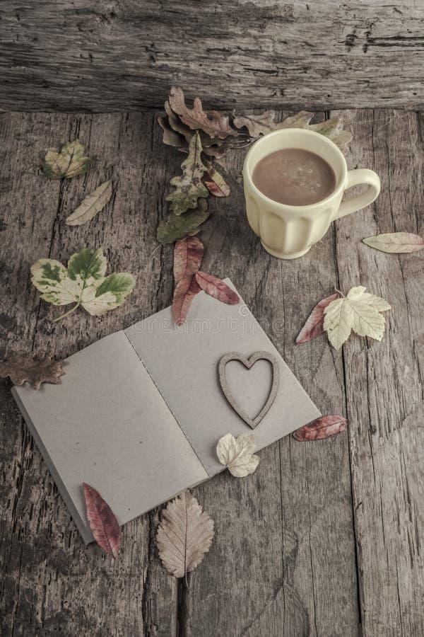 Caderno e café na tabela de madeira decorada com folhas secadas foto de stock royalty free