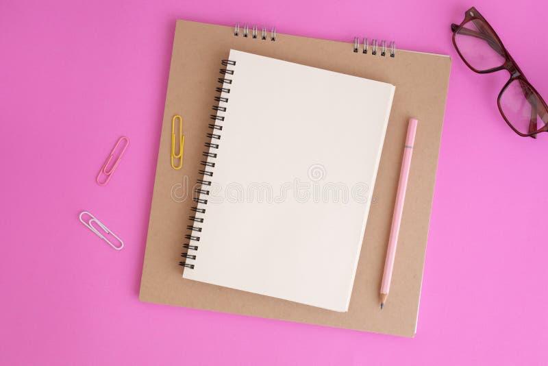 Caderno e lápis vazios no fundo cor-de-rosa, foto colocada lisa do caderno para sua mensagem fotos de stock