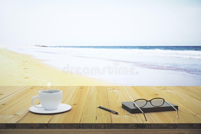 Caderno e vidros da xícara de café em uma tabela de madeira no beac imagem de stock