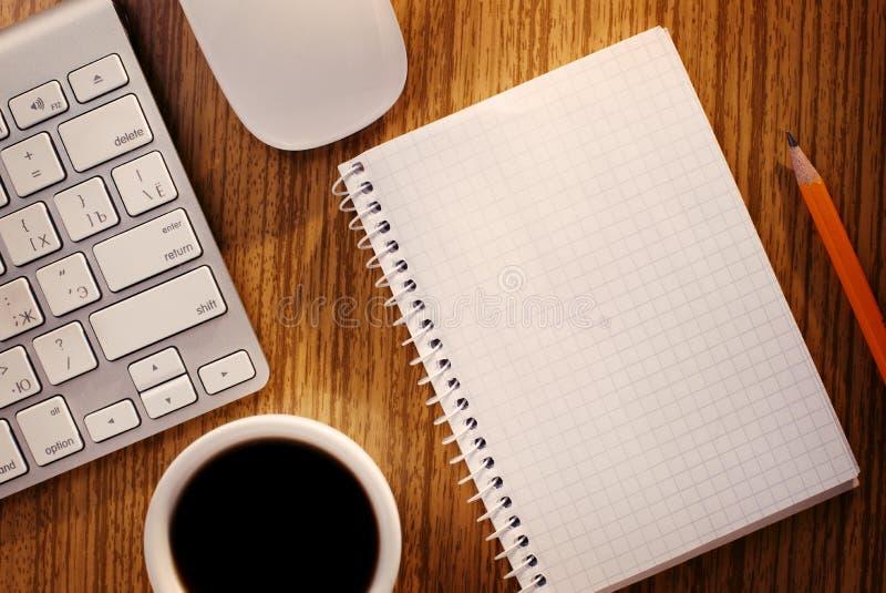 Caderno e xícara de café perto do teclado de computador imagens de stock