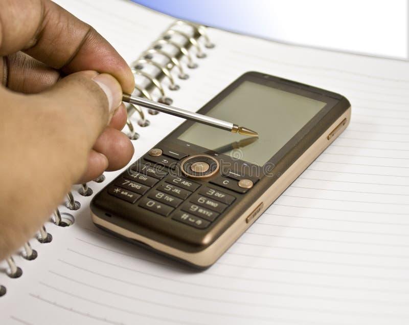 Caderno em branco, estilete, telefone móvel, mão fotografia de stock