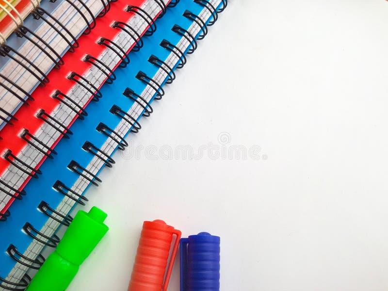 Caderno espiral com penas de marcadores Pilha de cadernos coloridos isolados no fundo branco Colorido - azul, vermelho, verde, br foto de stock royalty free