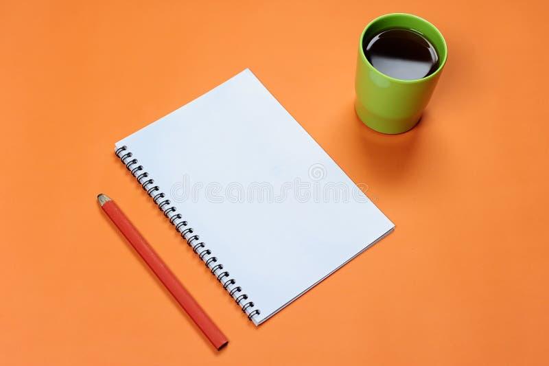 Caderno espiral da placa da vista superior com o copo do lápis e de café no fundo pastel alaranjado Almofada de escrita vazia par foto de stock royalty free