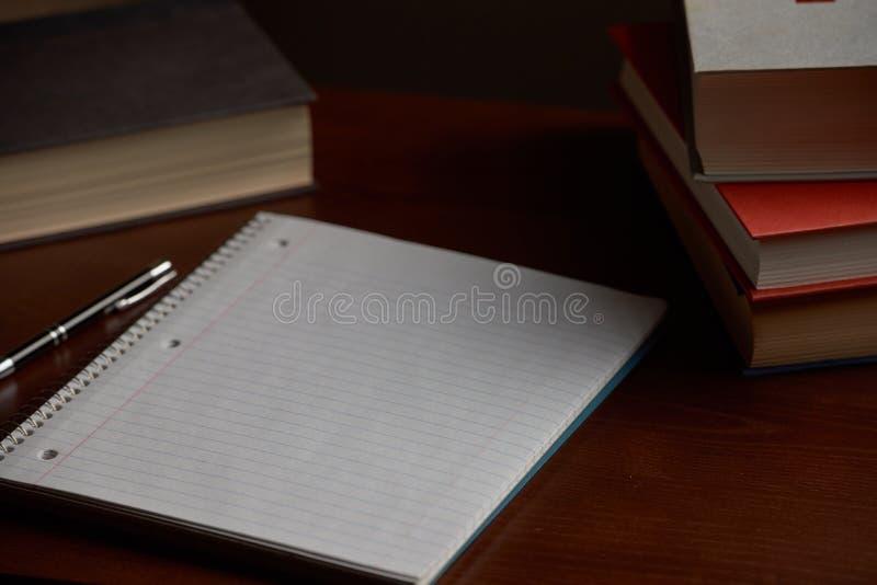 Caderno espiral na mesa com livros fotografia de stock royalty free