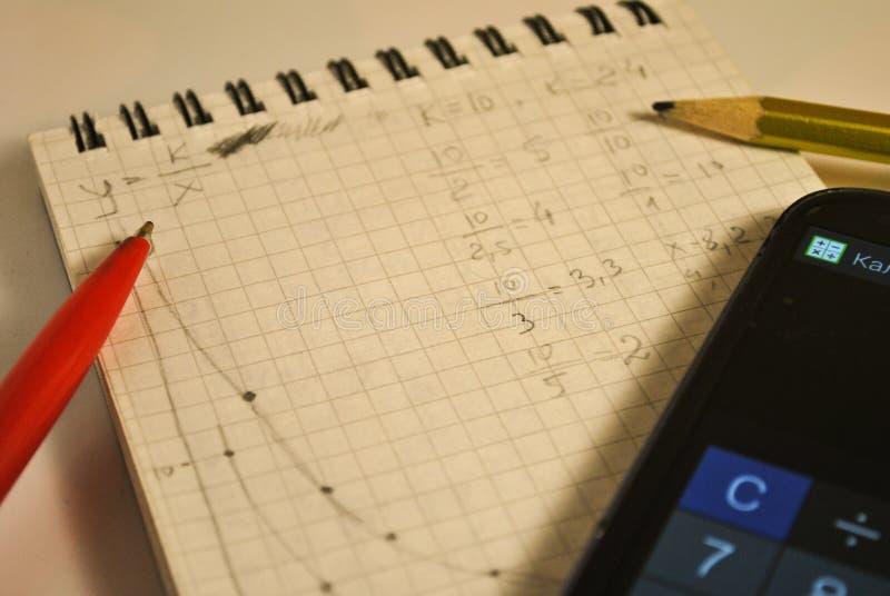 Caderno, fórmulas, gráficos matemáticos, trabalhos de casa, telefone celular fotografia de stock