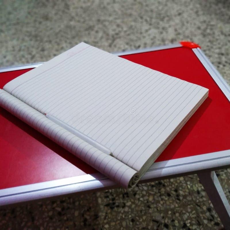 Caderno na tabela do estudo imagem de stock