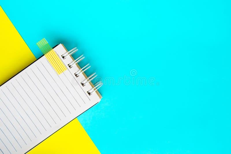 Caderno no fundo azul e amarelo foto de stock