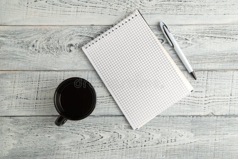 Caderno, pena e copo de papel do chá ou do café no fundo de madeira branco gasto do vintage A vista da parte superior Configura?? fotos de stock