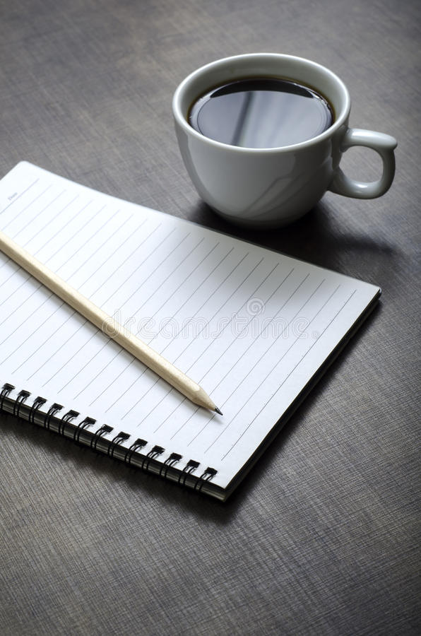 Caderno, pena e xícara de café brancos vazios na mesa foto de stock royalty free
