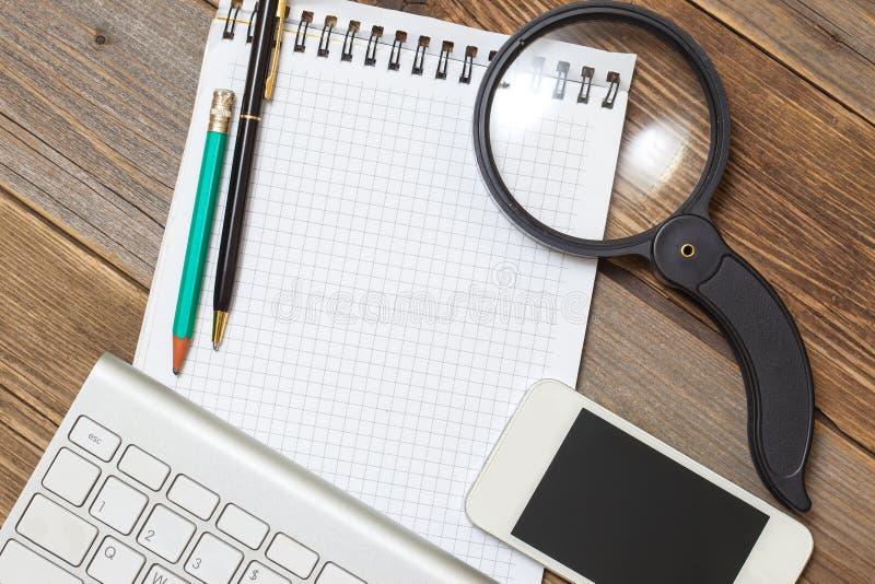 Caderno, teclado de computador, pena, lápis e lupa fotografia de stock