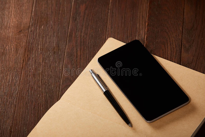 Caderno, telefone e pena no fundo de madeira marrom imagens de stock royalty free