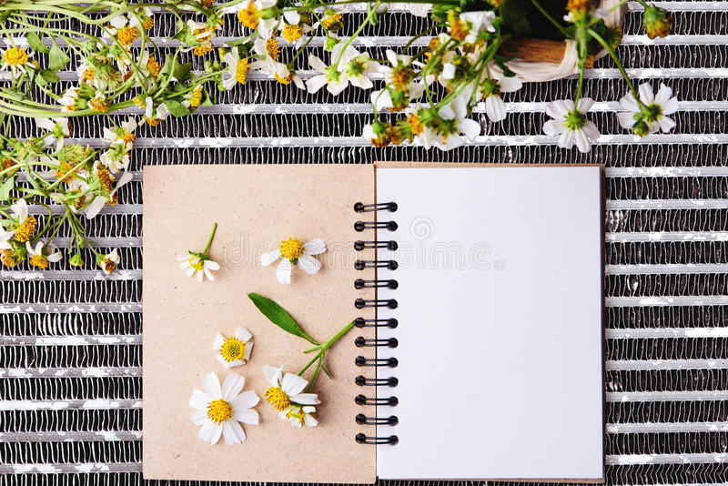 Caderno vazio com ket da flor branca e dos bas da flor na tabela líquida de aço foto de stock royalty free