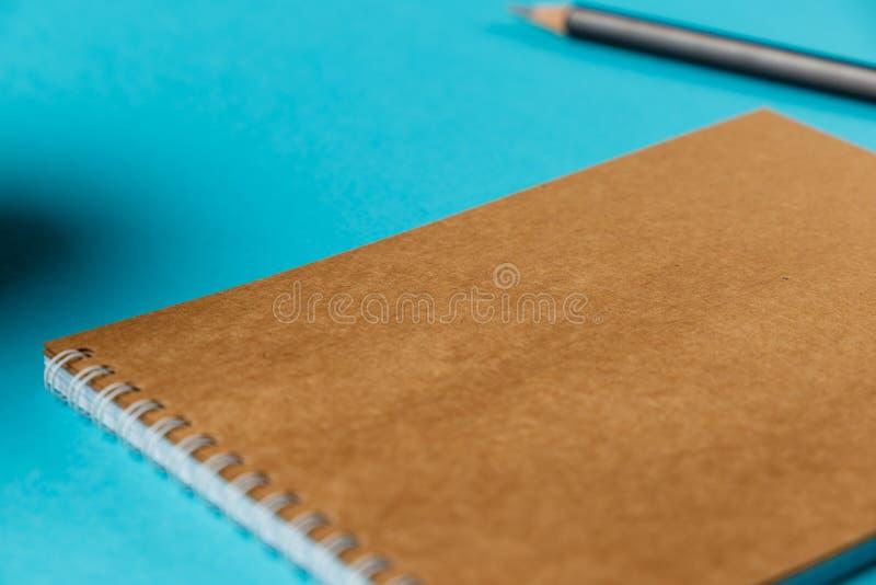 Caderno vazio com lápis e xícara de café no fundo azul workplace Copie o espa?o fotografia de stock