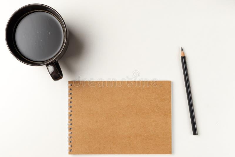 Caderno vazio com lápis e xícara de café no fundo branco workplace Copie o espa?o imagens de stock