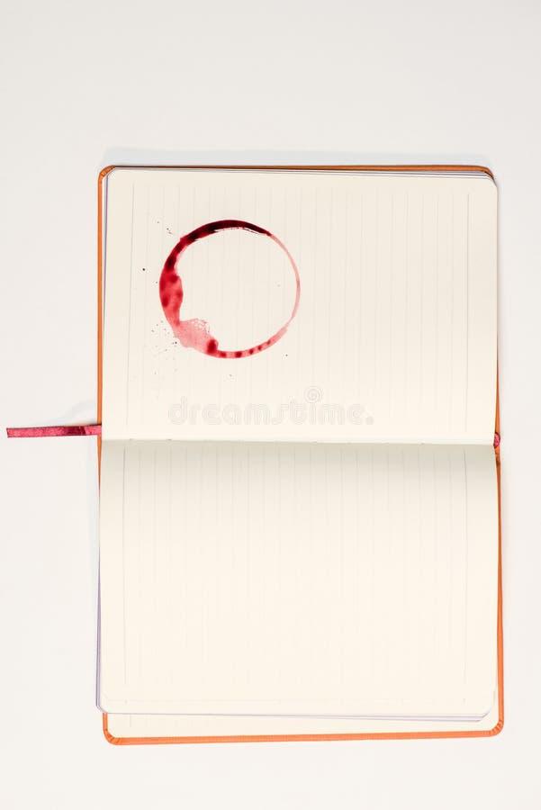 Caderno vazio com mancha do vinho tinto imagens de stock
