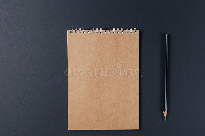 Caderno vazio com o lápis no fundo preto workplace Copie o espa?o Conceito m?nimo imagem de stock