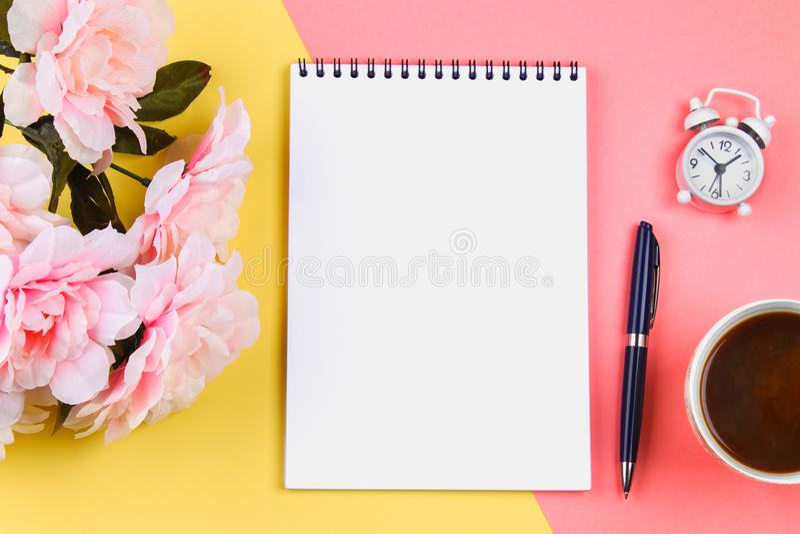 Caderno vazio com a pena azul no fundo pastel amarelo-cor-de-rosa modelo, quadro, molde foto de stock